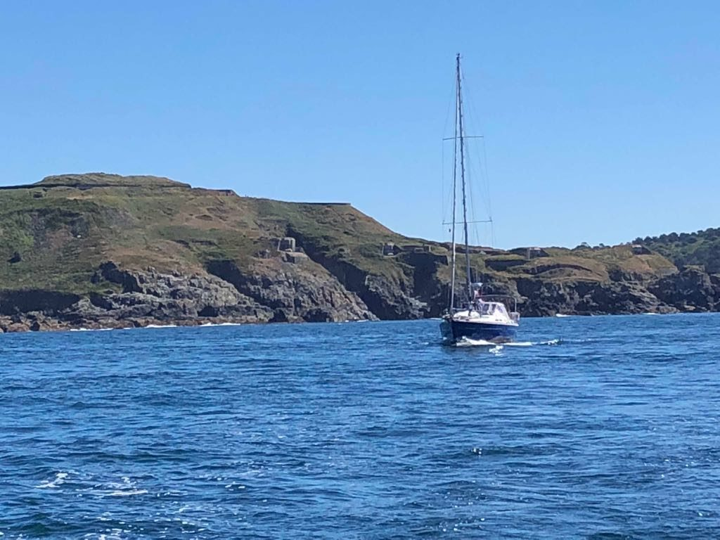 sv Phi met op de achtergrond de kust van Alderney